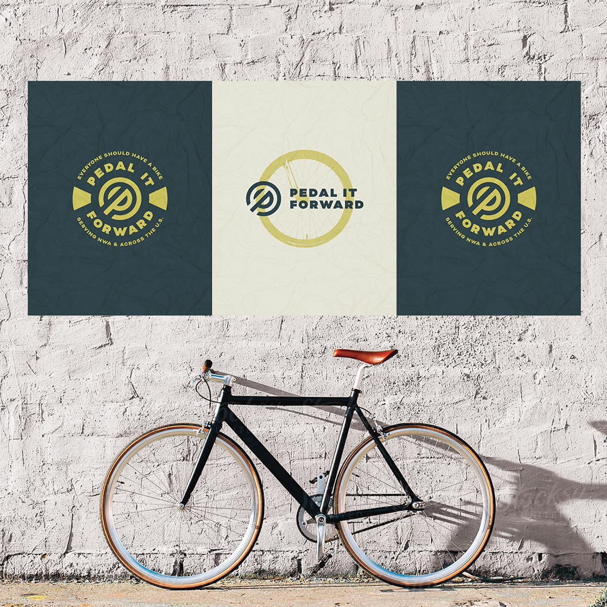 pedal it forward posters on wall with bike