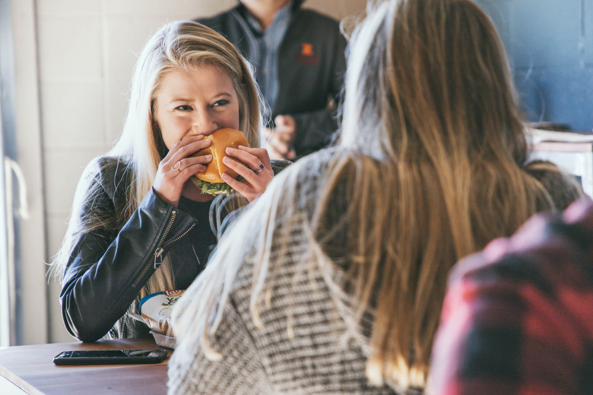 two women eating cheeseburgers
