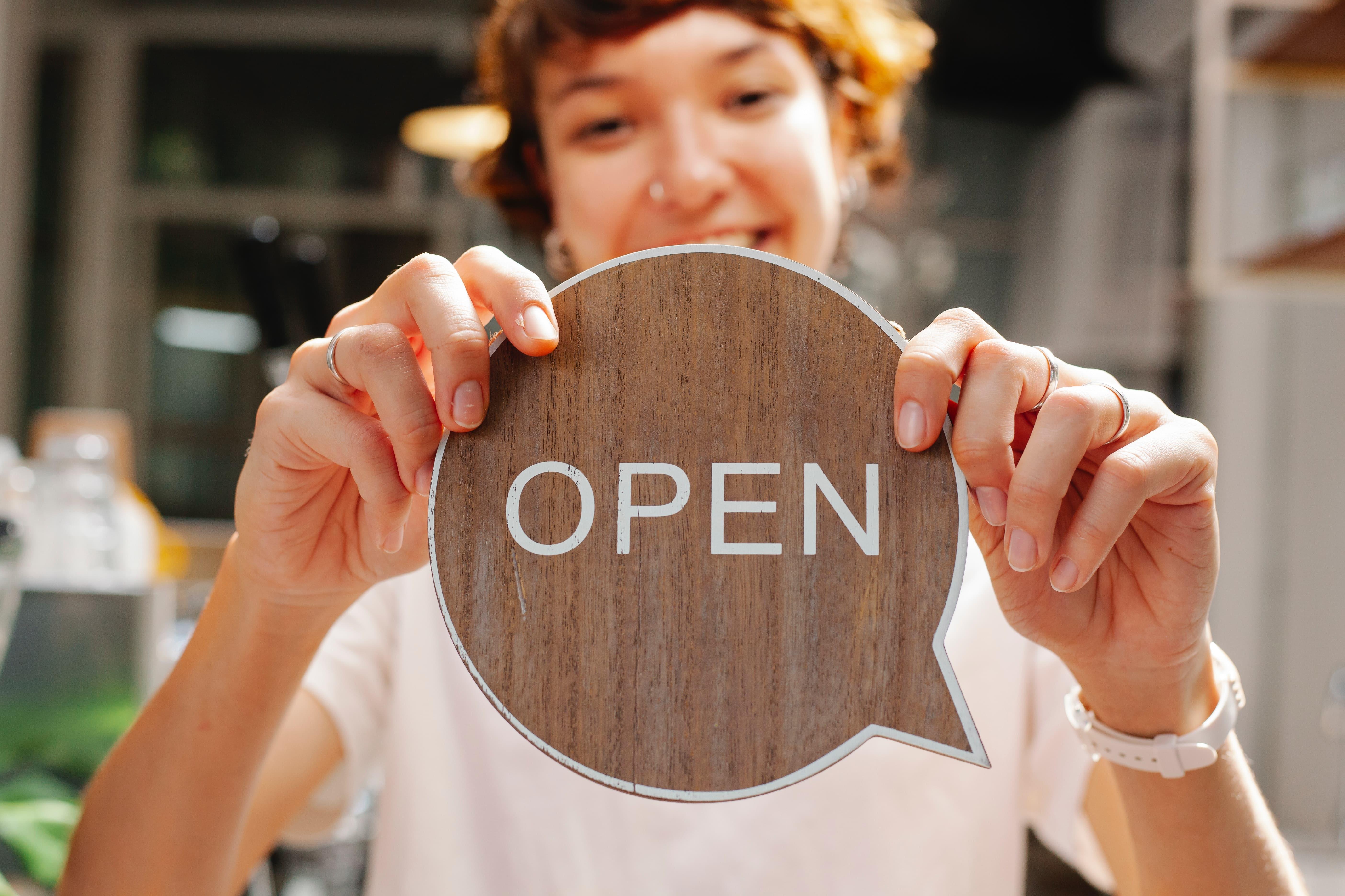 Girl holding open sign